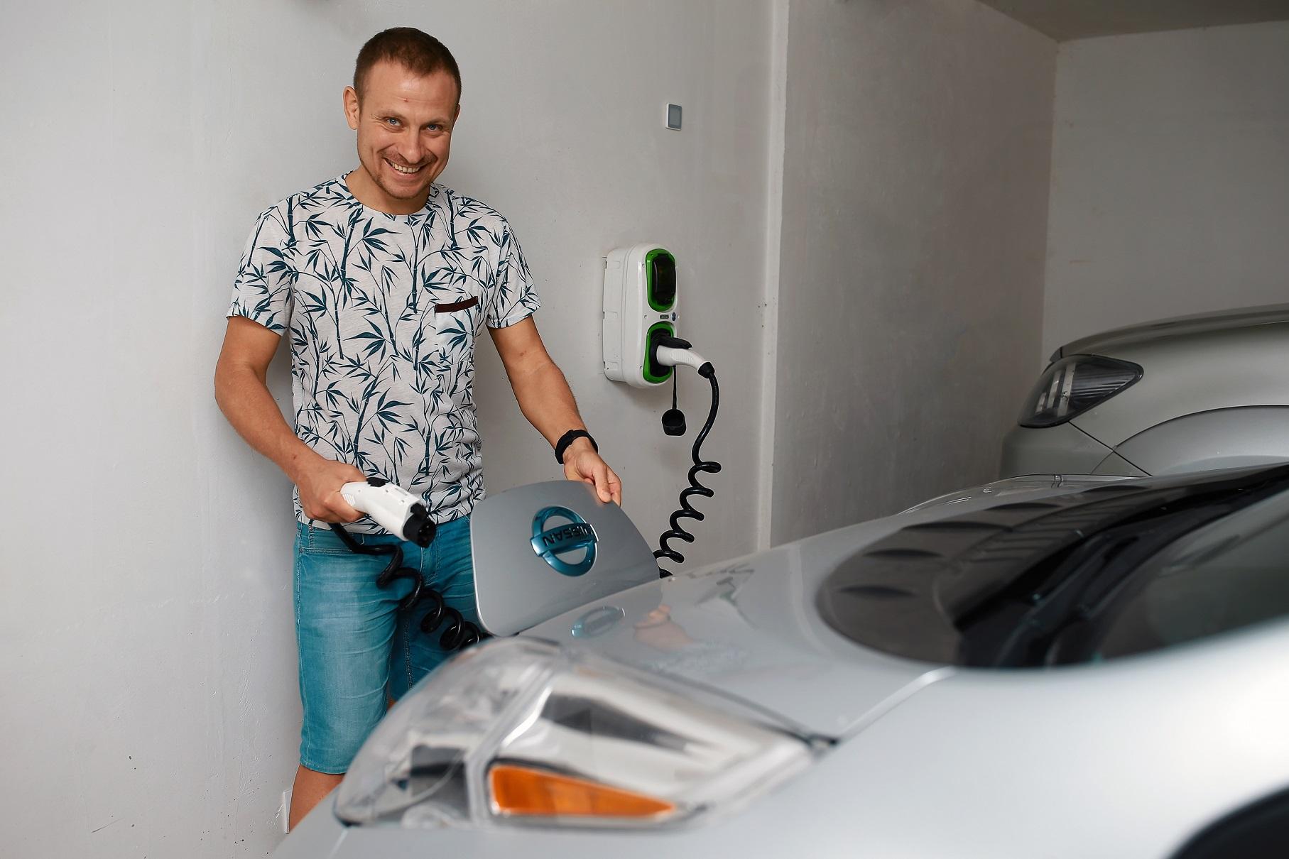 Maxim Ciumaş, entuziasmat de mașina sa personală, pe care o alimentează chiar de acasă, cu energie electrică de la o priză specială. Foto: agora.md