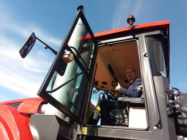 """Ministrul Agriculturii, Ion Perju, la volanul unui tractor """"Kirovets"""".Tractorul cel mic """"Kirovets"""" este dezmierdat Kiriușa."""